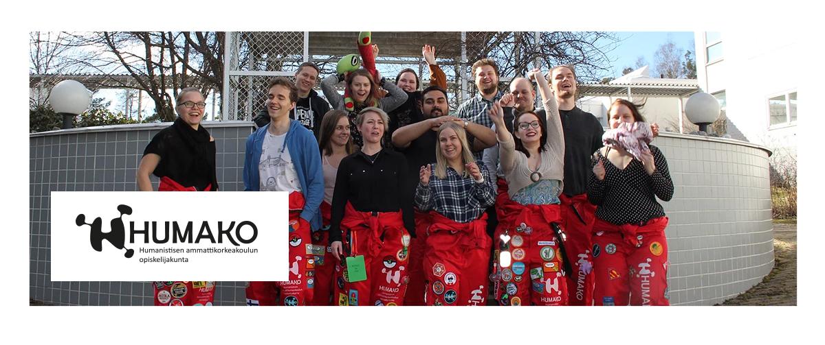 Riemukas, punaisiin opiskelijahaalareihin pukeutunut opiskelijaryhmä heiluttaa käsiään, hymyilee pihalla.