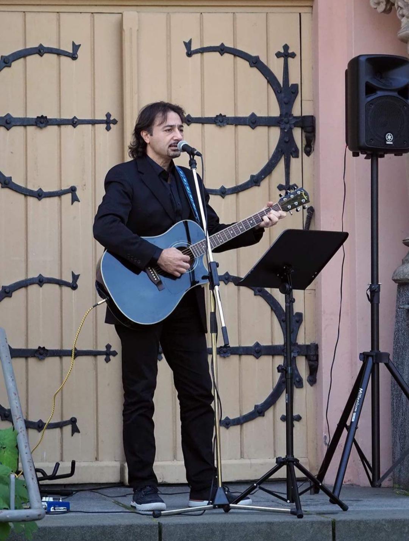 Mustaan pukuun pukeutunut, tummahiuksinen mies soittaa sinistä kitaraa ja lautaa mikrofonin edessä seisten, taustalla nuottiteline ja kaiutin, tapahtuma ulkona.