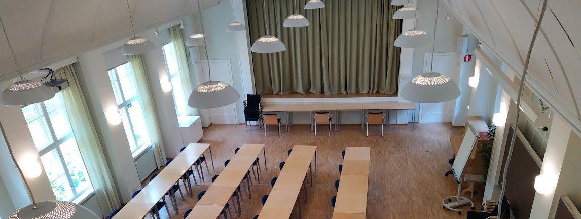 Yläviistosta otettu luokkakuva, jossa näkyy pöytärivistöjä, pyöreitä palavia kattolamppuja, ikkunarivistot seinustoilla ja päädyssä vihreän kankaan peittävä näyttämö. Kuva Kauniaisten kampukselta.