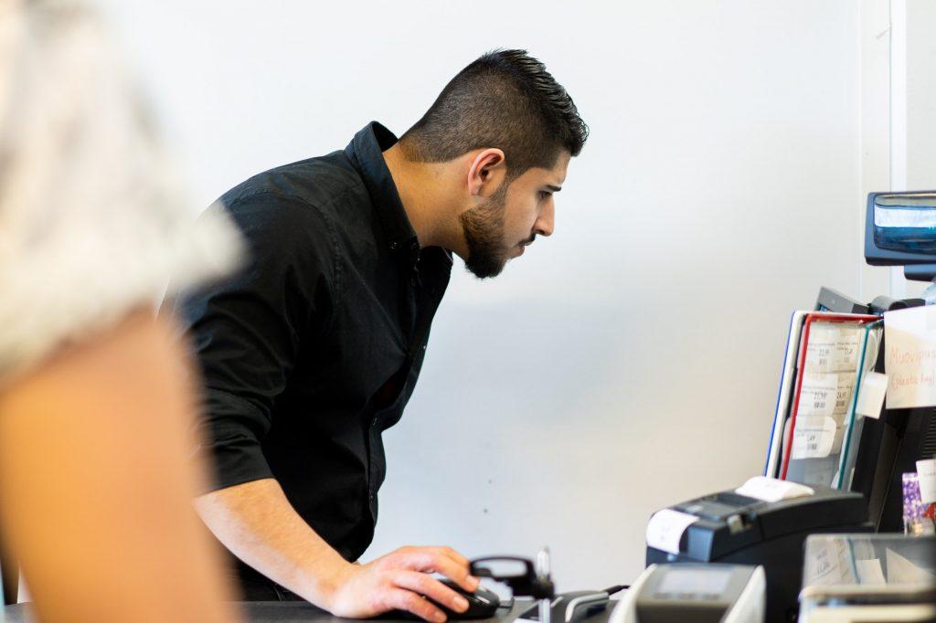 Mies mustassa paidassa katsoo kassakoneen näyttöä samalla, kun hänen kätensä on kuvan alalaidassa näkyvän hiiren päällä.