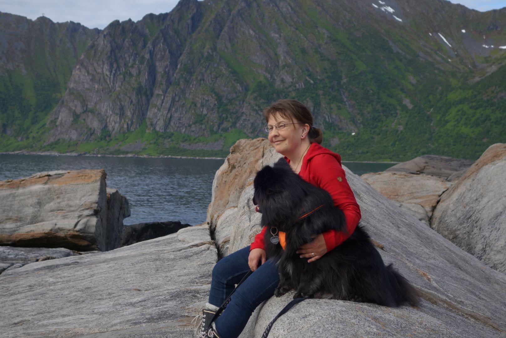 Punaiseen paitaan ja sinisiin farkkuihin pukeutunut nainen ja musta koira istuvat kivellä, järvimaisemassa.