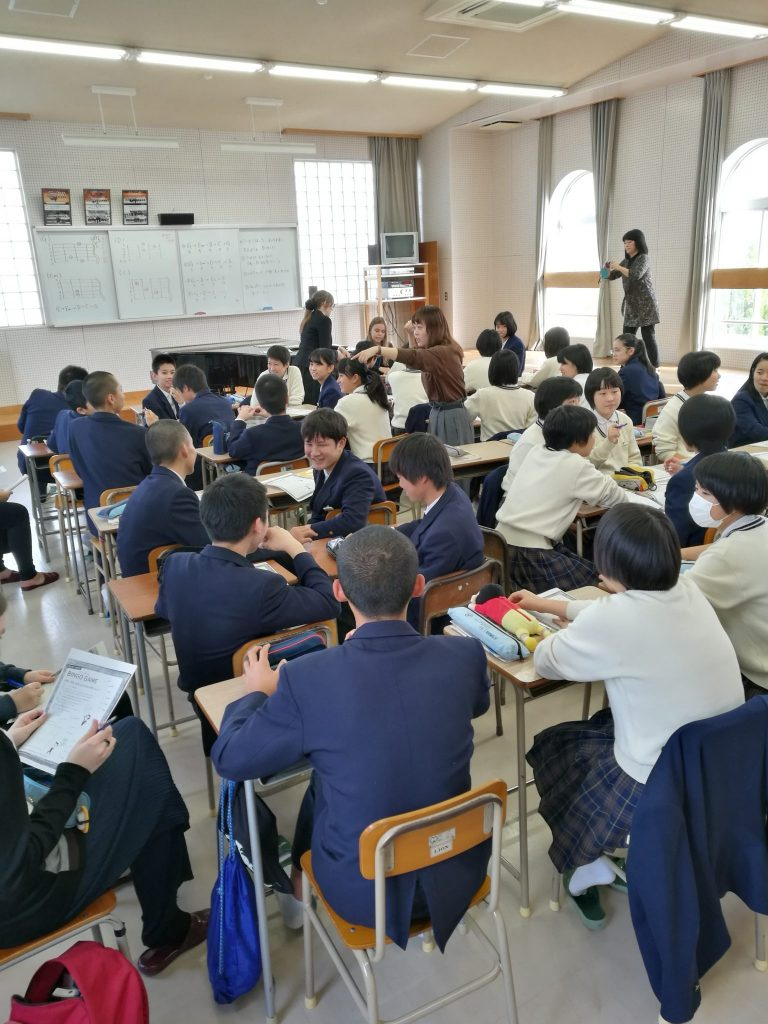 A lively group of Japanese students sitting by their desks in a classroom. Guitar chord instructions can be seen on a white board in front of the classroom.
