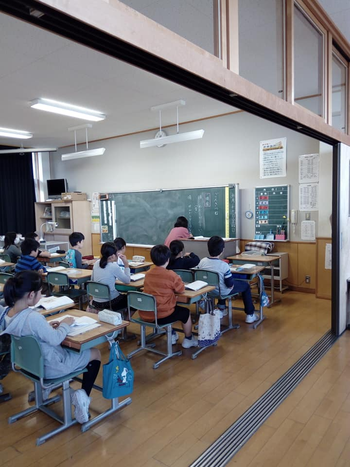 A japanese classroom pictured from the side, where 10 children can be seen sitting on their desks while a teacher is writing something on the chalkboard with a piece of chalk.