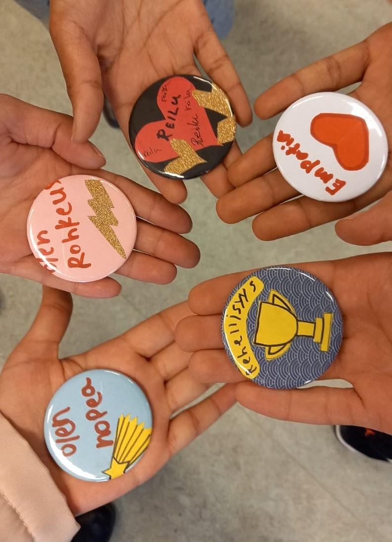 Kuvassa näkyy viidessä eri kädessä itse tehdyt pinssit, jotka kuvastavat tekijöiden osaamista kuvin ja sanoin. Vahvuudet ovat: nopeus, rohkeus, reiluus, empatia ja rehellisyys.