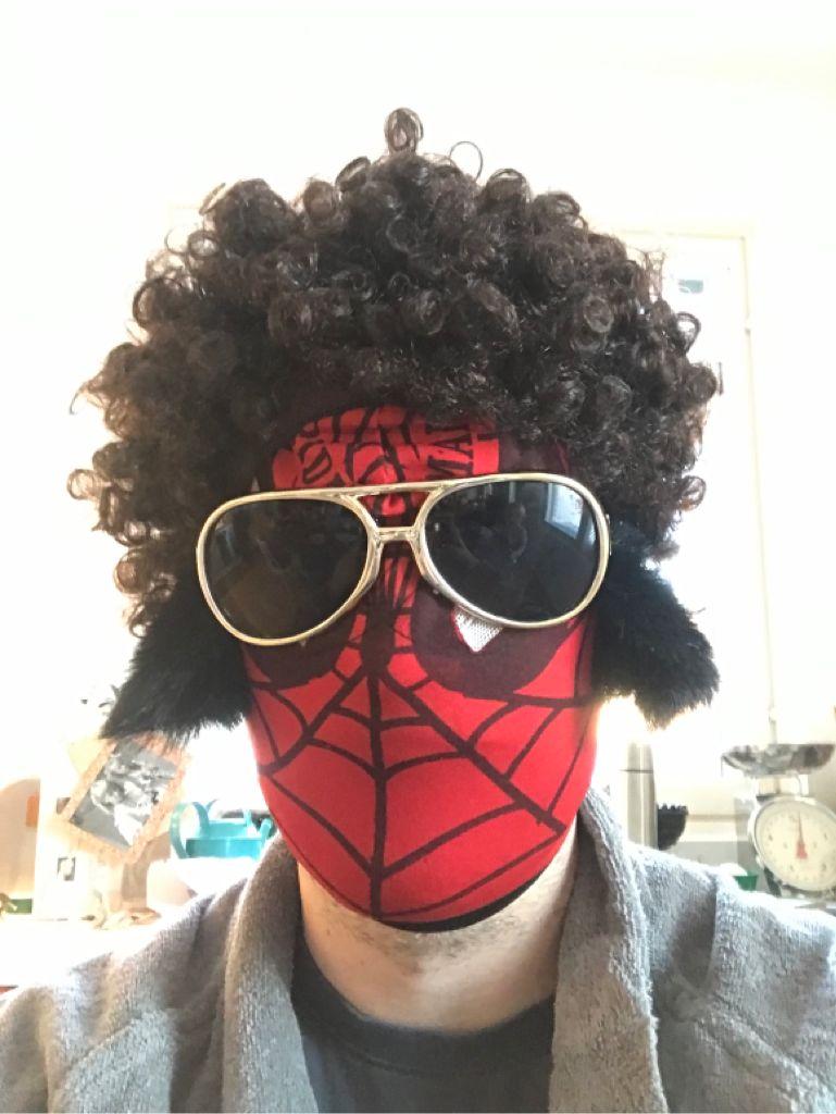 Harmaahupparinen mies, jolla punainen Spiderman naamio, isot valkosankaiset aurinkolasit, tumman ruskea, tuuhea peruukki.