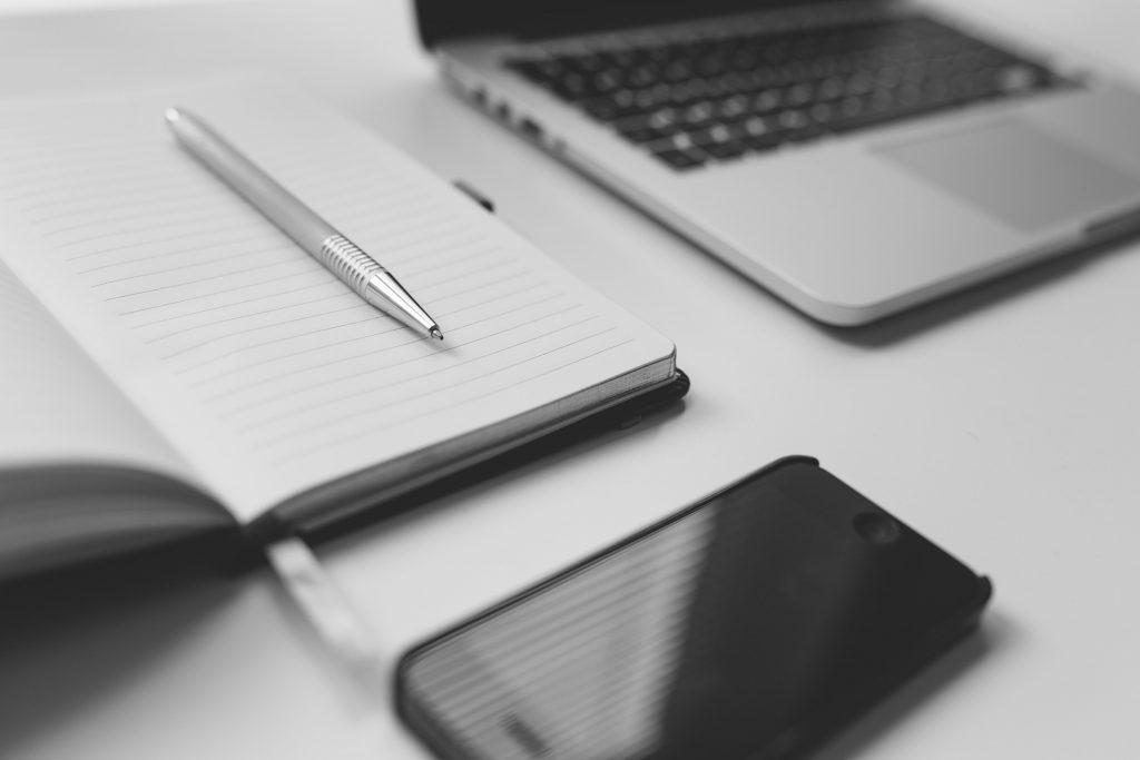 Mustavalkoinen lähikuva pöydästä, jossa kynä, muistilehtiö, tietokone ja kännykkä, tavarat näkyvät osittaisina.