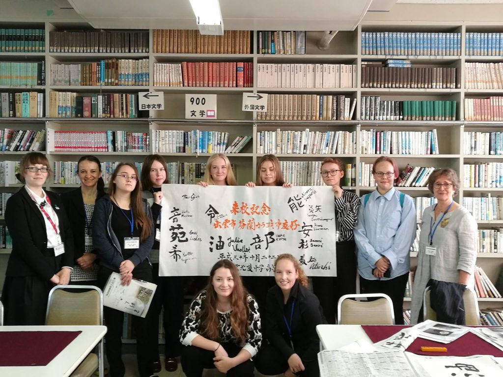 A group of students and supervisors standing in front of multiple bookshelves with four of them holding a white sign with Japanese symbols on it.