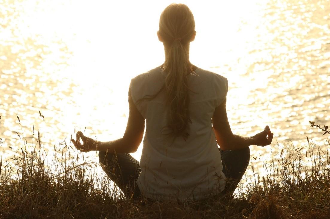 Nainen, jolla on poninhäntä istuu selkä kameraan päin jooga-asennossa jalat ristissä nurmikon päällä ja katselee auringon valaisemaa merta.