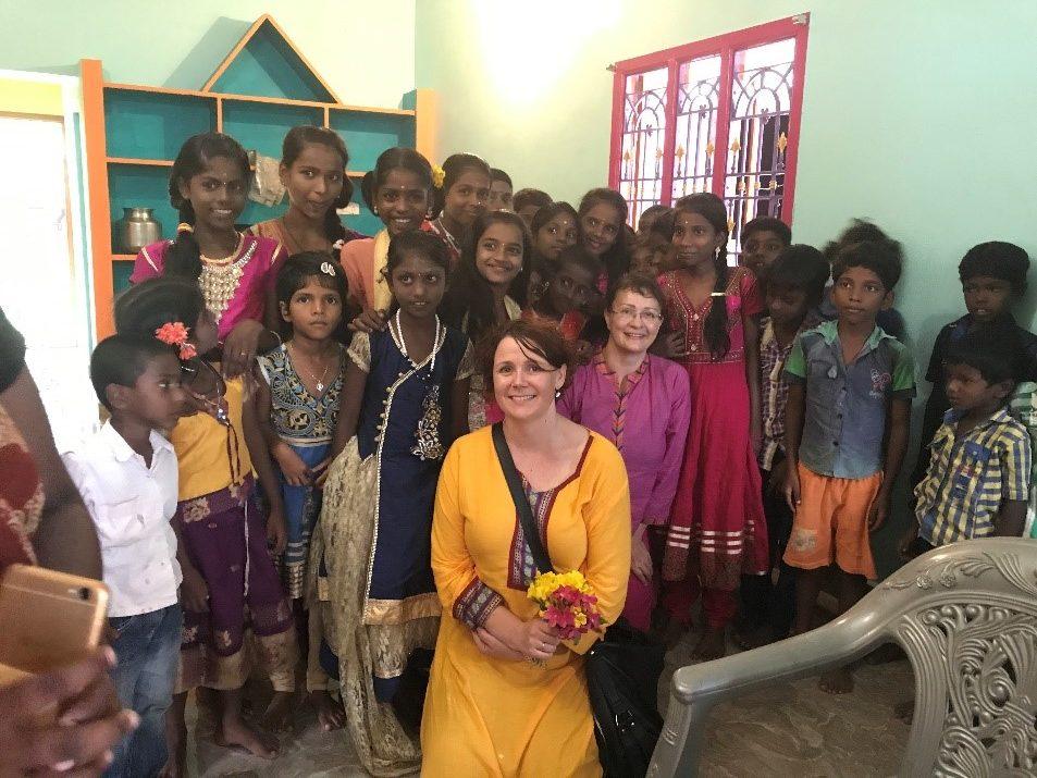 Kaksi naista värikkäissä mekoissa hymyilee intialaisen lapsiryhmän ympäröimänä siniseinäisessä talossa.
