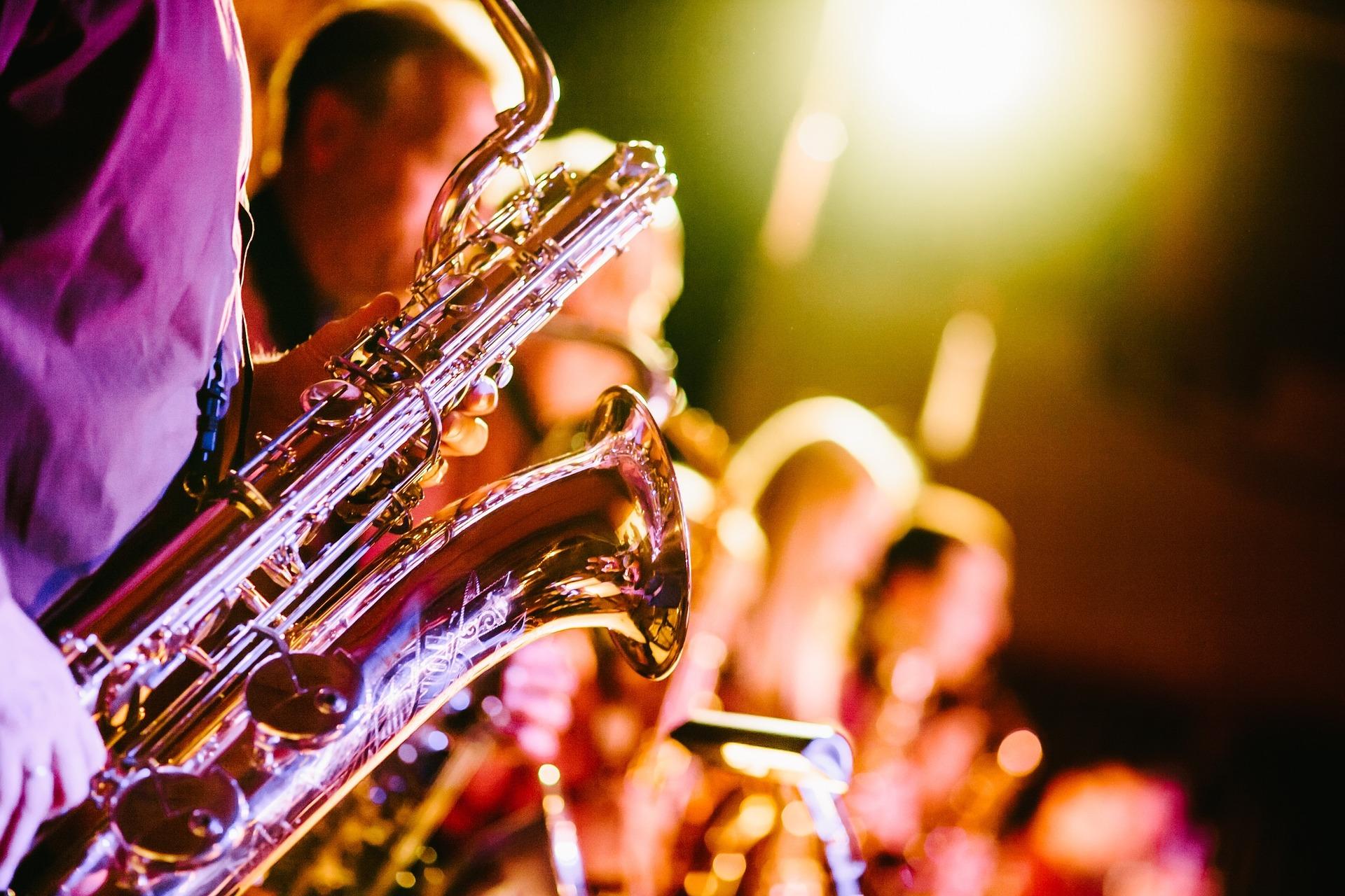 Värilähikuva saksofoneista, taustalla rivi soittajia.