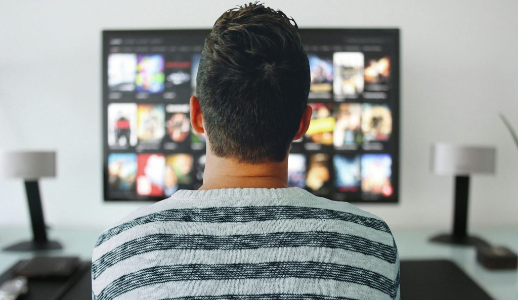 Mies raidallisessa paidassa katsoo televisiota selkä käännettynä kameraan. Television molemmin puolin on harmaat kaiuttimet.