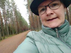 Hiekkatiellä kulkeva nainen lähikuvassa, hattu ja vihertävä takki, Liisa Mertala.