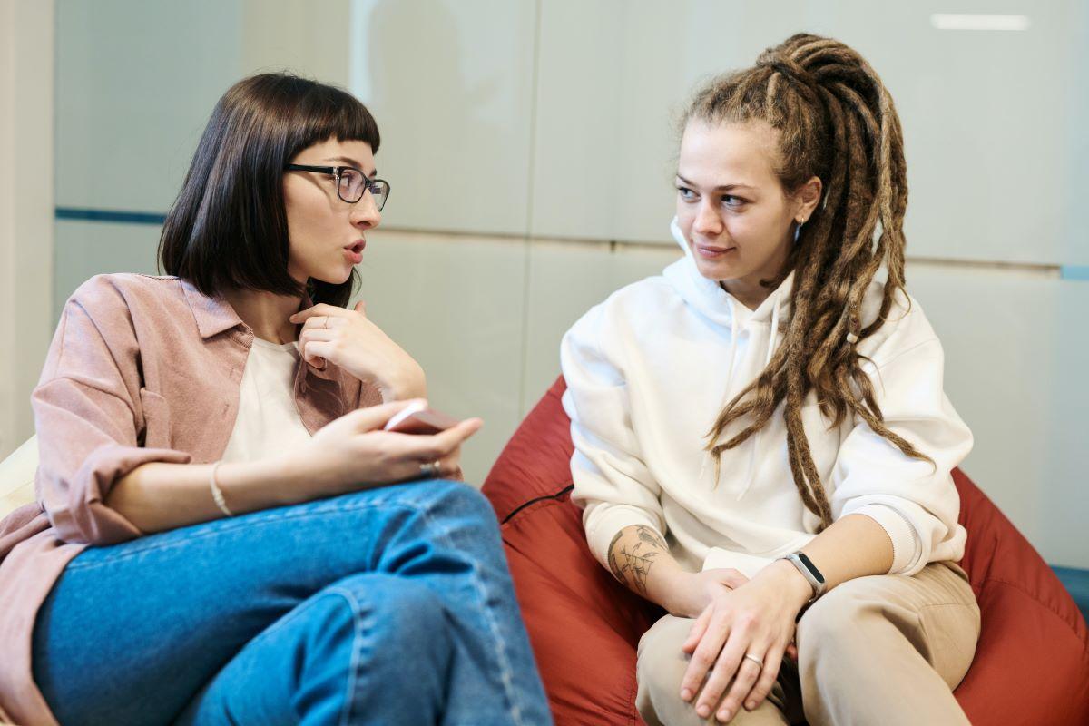 Kaksi naista istuu sohvalla vierekkäin.